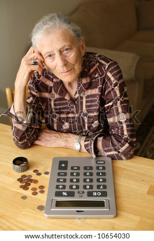 Senior woman counting money with calculator