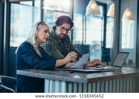 Senior woman discussing work with male colleague. Two business associates working together in office and talking over a business report.