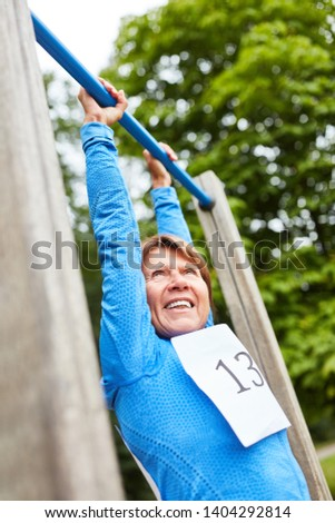 Senior woman doing a pull-up on the trim you course in nature