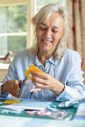 Senior Woman Doing Craft Scrapbooking Or Making Greetings Card  At Home