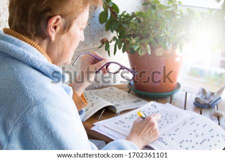senior woman doing crossword puzzles or hobbies sitting Foto stock ©