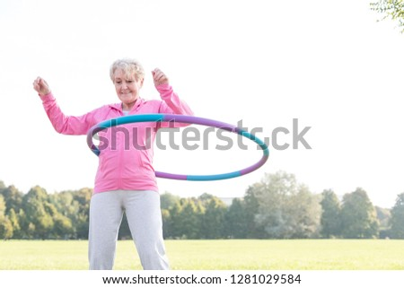 Senior woman doing gymnastic with hula hoop in park #1281029584