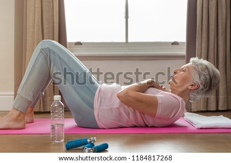 Senior woman doing sit ups on yoga mat at home. Fit healthy old woman doing abdomen crunches at home. Elderly woman keeping fit by exercising for staying healthy.