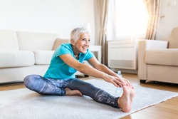 senior woman doing warmup workout at home. Fitness woman doing stretch exercise stretching her legs,quadriceps .Elderly woman living an active lifestyle.