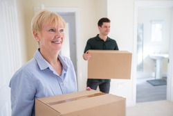 Senior Woman Downsizing In Retirement Carrying Boxes Into New Home On Moving Day With Removal Man Helping