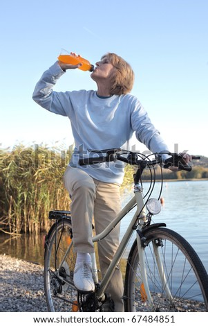 Senior woman drinking an energy drink on a bicycle with lake on the background