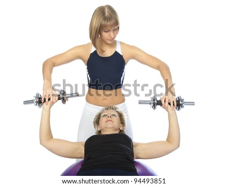 senior woman engaged in fitness with a trainer on the ball with dumbbells