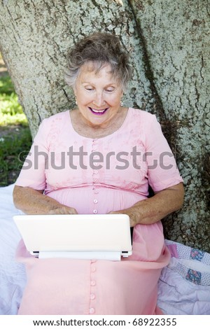 Senior woman enjoys using her netbook computer outdoors.