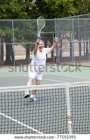 Senior woman excited about winning a tennis match.