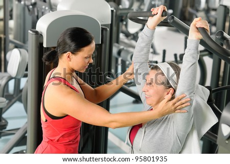 Senior woman exercise on shoulder press machine with personal trainer - stock photo