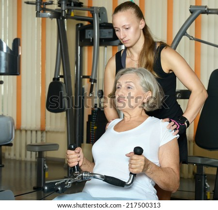 Senior woman exercising in gym with sport coach