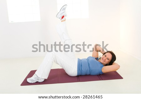 Senior woman exercising on mat. She's lying with raised leg. She's smiling and looking at camera. Side view.