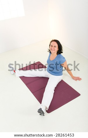 Senior woman exercising on mat. She's smiling and looking at camera. High angle view.