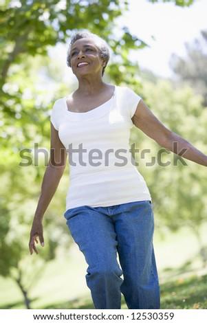 Senior woman exercising outside in park