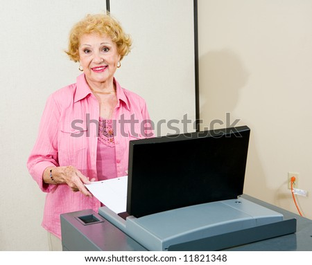 Senior woman feeding her ballot into a new optical scan voting machine.  Authentic image shot at supervisor of elections. - stock photo