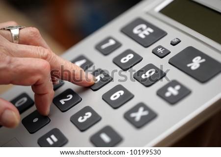 Senior woman fingers pressing keys on big calculator