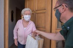 Senior woman gets shopping bag from neighborhood assistance