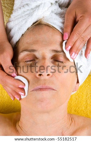 Senior woman getting a cleansing face at spa retreat