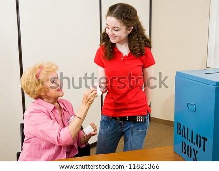 Senior woman giving an I Voted sticker to a young first time voter.