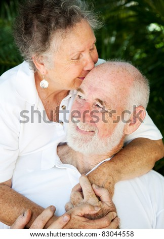 Senior woman giving her husband a kiss on the forehead.