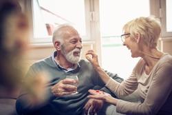 Senior woman giving her husband medication vitamins supplement.