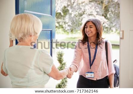Senior woman greeting female care worker making home visit #717362146