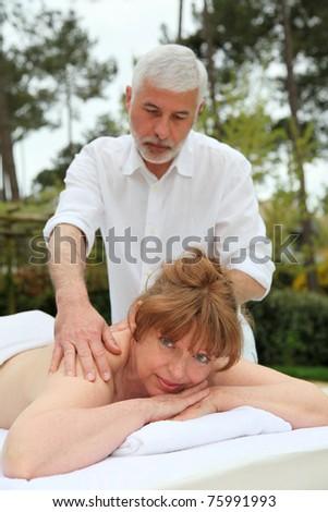 Senior woman having a massage in spa center