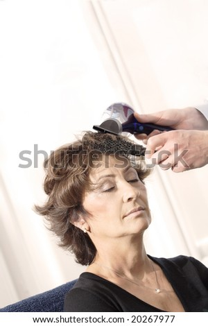 Senior woman having haircut in barber shop. - stock photo