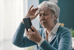 Senior woman having vision problems, she can't read the messages on her smartphone