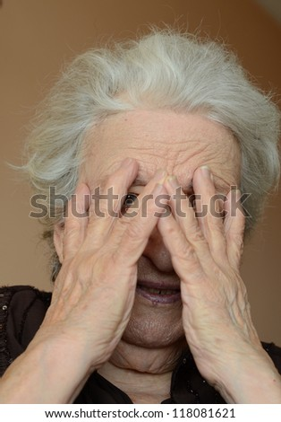 senior woman hiding her face with her hands