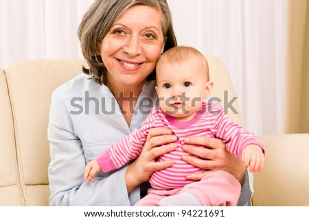 Senior woman hold little baby girl cute smiling close-up