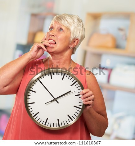 Senior Woman Holding A Clock And Thinking, Indoor