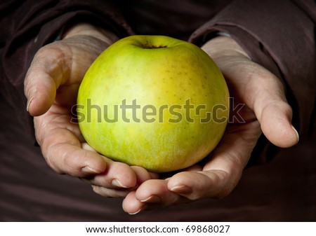 Senior Woman Holding Apple in her Palms. - stock photo
