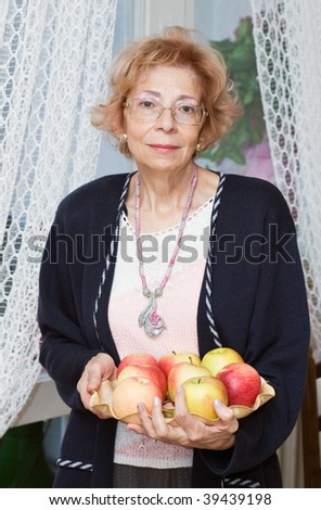 Senior  Woman holding bowl with apples