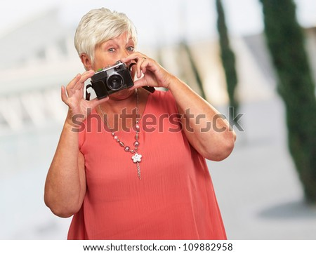 Senior Woman Holding Camera, Outdoor