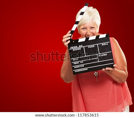 Senior Woman Holding Clapper Isolated On Red Background