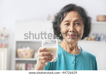 Senior woman holding glass of milk, offering to camera. PS: shallow depth of field