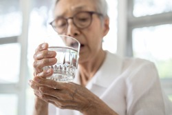 Senior woman holding glass of water,hand shaking while drinking water,elderly patient with hands tremor uncontrolled body tremors,symptom of essential tremor,parkinson's disease,neurological disorders
