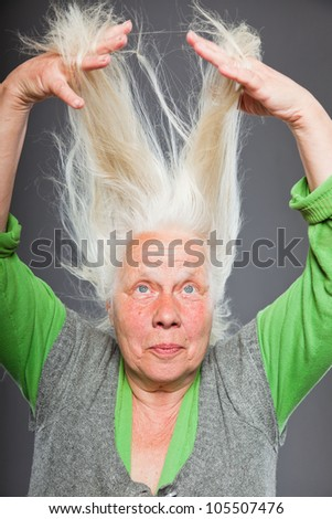 Senior woman holding hands in her hair. Spiritual looking. Studio shot isolated on grey background.