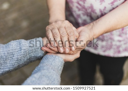Senior woman holding hands of a young person in  the park on a sunny day - Mother showing love and affectionate gesture for her daughter - Concept image for support and care