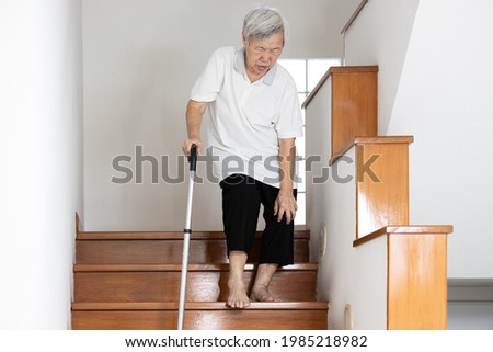 Senior woman holding her pain knee with hand while walking down the stairs,elderly suffering from Osteoarthritis of the knee,Rheumatic disease,painful in the knee joint or bone degeneration in old age Photo stock ©