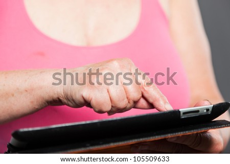 Senior woman holding tablet long grey hair. Studio shot. Isolated on grey background.