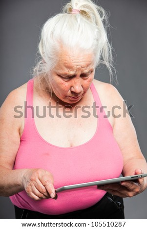 Senior woman holding tablet long grey hair. Studio shot. Isolated on grey background.