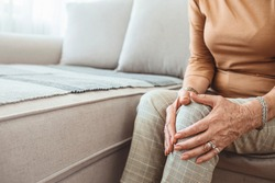 Senior woman holding the knee with pain. Old age, health problem and people concept - senior woman suffering from pain in leg at home. Elderly woman suffering from pain in knee at home