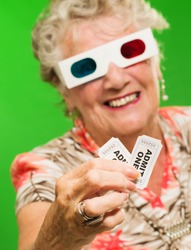 Senior Woman Holding Two 3d Movie Tickets On Green Background