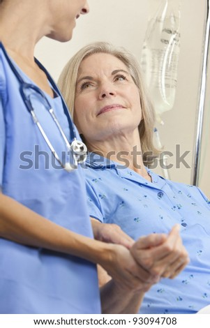 Senior woman in a hospital bed having her pulse taken by a female doctor with stethoscope