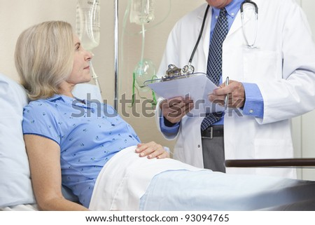 Senior woman in a hospital bed having talking to male doctor with stethoscope and clipboard