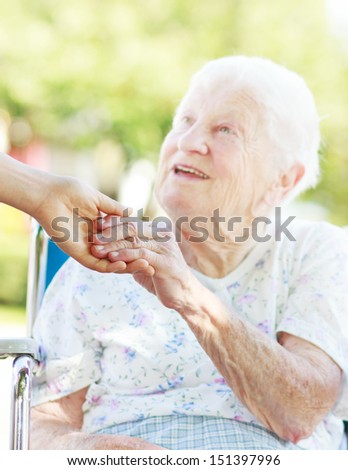 Senior woman in a wheelchair outside holding hands with her caretaker