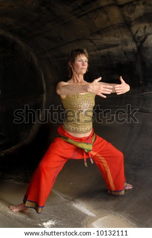 Senior Woman in Asian Yoga Qi Gong influenced pose in a rust cylinder.