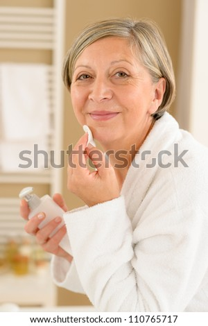 Senior woman in bathroom looking at camera cleaning facial cream